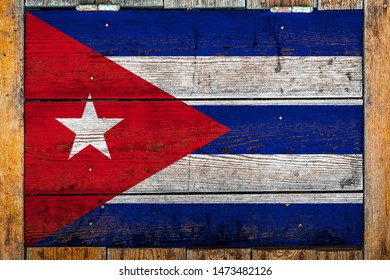 National flag of Cuba on a wooden wall background.The concept of national pride and symbol of the country.Flag painted on a wooden fence with metal nails.
