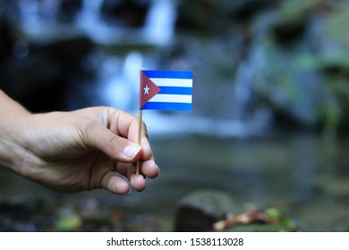 National flag of Cuba on wooden stick. Young boy holds national athem near waterfall on stream in autumn times. Concept of humanity and nature. Republic of Cuba in hand.  Flag for packet.