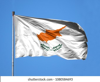 National flag of Cyprus on a flagpole in front of blue sky