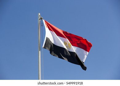 National flag of Egypt on a flagpole in front of blue sky