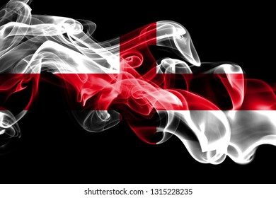 National flag of England made from colored smoke isolated on black background. Abstract silky wave background