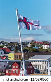 National Flag of Faroe islands country  with the background of Torshavn city buildings and blue sky out of focus