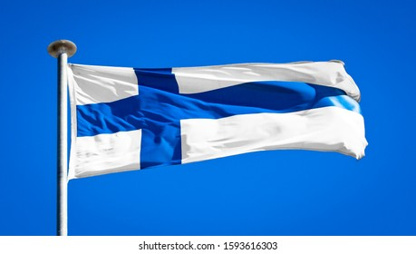 The national flag of Finland. Known as the Blue Cross Flag. Finnish flag blowing in strong wind against a pure blue sky. Symbol of national patriotism.