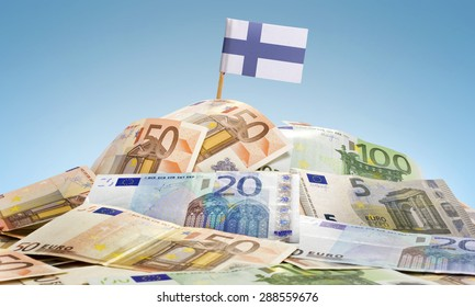 The national flag of Finland sticking in a pile of mixed european banknotes.(series)