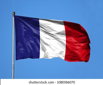 National flag of France on a flagpole in front of blue sky