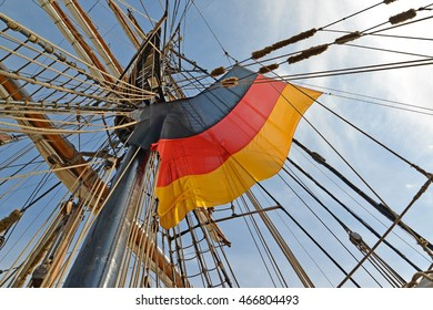 National flag of Germany flutters among ropes of the sailing vessel