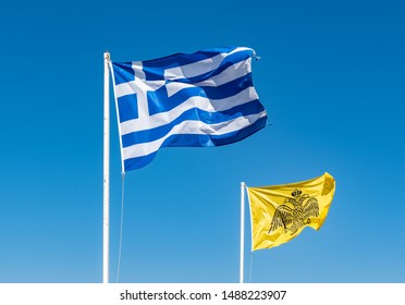 National Flag of Greece and Byzantine Flag against blue sky background.