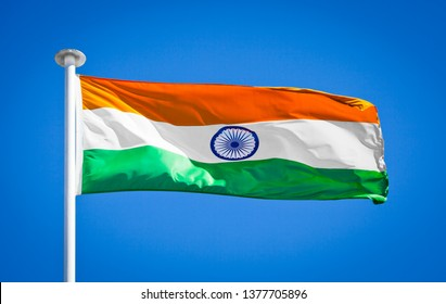 National flag of India. Indian flag blowing in strong wing against pure blue sky. Symbol of national patriotism