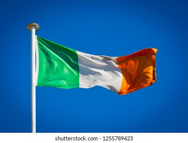 The national flag of Ireland frequently referred to as the Irish tricolour blowing in strong wind against pure blue sky.