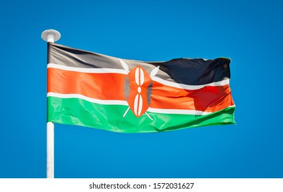 National flag of Kenya. Showing Maasai shield and crossed spears. Kenyan flag blowing in strong wind against a pure blue sky. Symbol of national patriotism