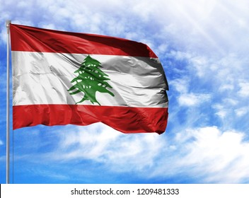 National flag of Lebanon on a flagpole in front of blue sky