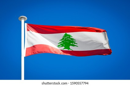 The national flag of Lebanon. Showing green cedar. Lebanese flag blowing in strong wind against a pure blue sky. Symbol of national patriotism