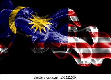 National flag of Malaysia made from colored smoke isolated on black background. Abstract silky wave background