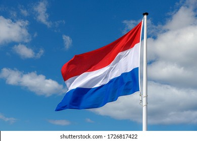 National flag of the Netherlands with horizontal tricolour of red, white and blue, Dutch flag waving on the air in a sunny day and blue sky background.