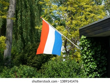 National flag of the Netherlands on the side of a house, waving in the wind.