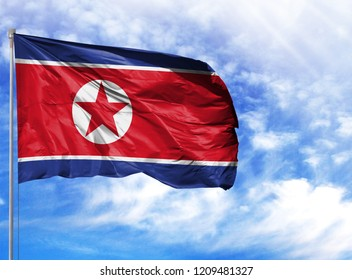 National flag of North Korea on a flagpole in front of blue sky