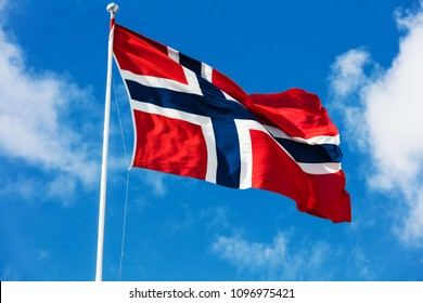 national flag of Norway blowing in the wind in front of a blue sky