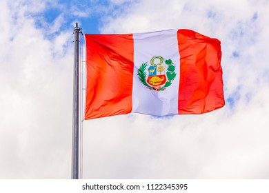 The national flag of Peru flutters in the wind against a blue cloudy sky.