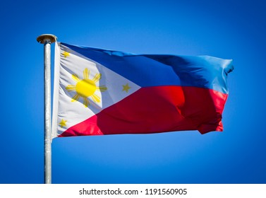 National Flag of the Philippines blowing in strong wind against pure blue sky. Pambansang Watawat ng Pilipinas, symbol of national patriotism.