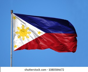 National flag of Philippines on a flagpole in front of blue sky