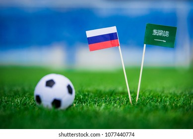 National flag of Russia and Saudi Arabia on Football pitch. Football ball on green grass.