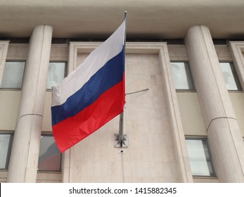 The national flag of the Russian Federation is attached to the wall of the building
