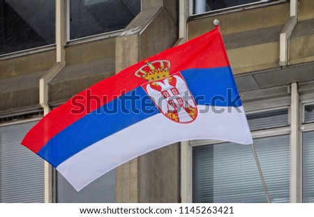 The national flag of Serbia flutters in the wind with modern architecture in background in Belgrade Serbia.