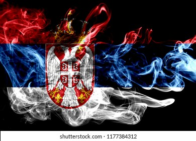 National flag of Serbia made from colored smoke isolated on black background. Abstract silky wave background.