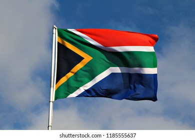National flag of South Africa on a flagpole in front of blue sky.