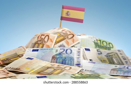 The national flag of Spain sticking in a pile of mixed european banknotes.(series)