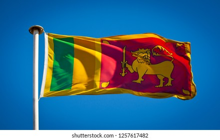 The national flag of Sri Lanka aka to as the Lion Flag blowing in strong wind against pure blue sky.