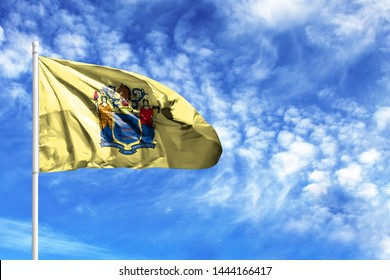 National flag State of New Jersey on a flagpole in front of blue sky