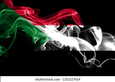 National flag of Sudan made from colored smoke isolated on black background. Abstract silky wave background
