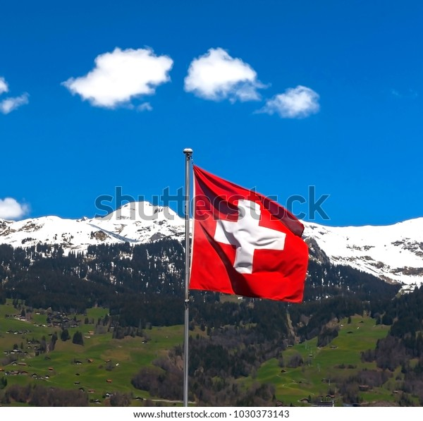 National flag in Swiss Alps on a sunny day