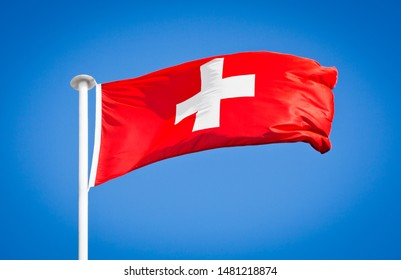 National flag of Switzerland. Known as the Swiss cross. Swiss flag blowing in strong wind against a pure blue sky. Symbol of national patriotism.