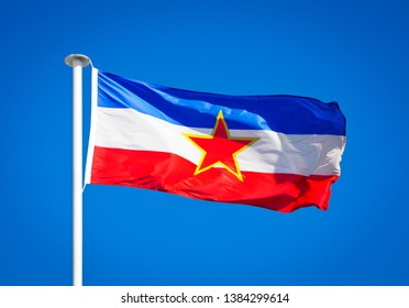 The national flag of Yugoslavia blowing in strong wing against pure blue sky. Symbol of national patriotism. Official flag of the Yugoslav state from 1918 to 1992.