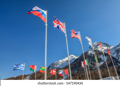 National flags of Russia, UK, USA, Greece and other countries wave in the wind as a friendship symbol on snowy mountains peak and blue sky background. Various fluttering national flags on flagpoles