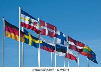 The National flags of the states around the Baltic Sea and the  flag of the European Union flying in the wind in front of a clear blue sky.