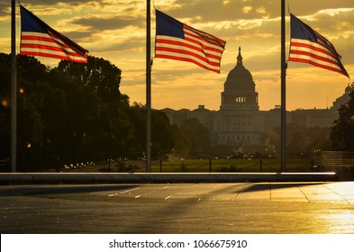 National flags and United States Capitol Building in a dramatic cloudy sunrise - Washington D.C. United States of America