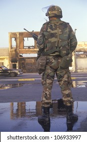 National Guardsman standing in front of burned business after 1992 riots, South Central Los Angeles, California