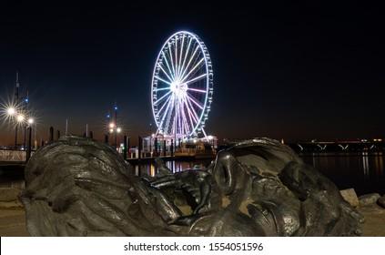 National Harbor, Maryland - 6 November 2019: Illuminated Capital Wheel with giant face of The Awakening at National Harbor Washington DC at sunset