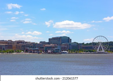 National Harbor photographed from Woodrow Wilson Bridge. National Harbor waterfront under blue cloudy sky in Maryland, USA