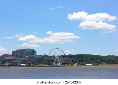 National Harbor photographed from Woodrow Wilson Memorial Bridge. National Harbor waterfront with Ferris wheel under a blue cloudy sky in Maryland, USA