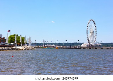 NATIONAL HARBOR, USA - JULY 4, 2014: Harbor pier with Ferris and the waterfront development on July 4, 2014 in National Harbor, USA. The town located along the Potomac River in Prince George's County.