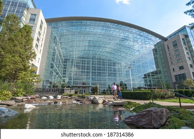 NATIONAL HARBOR, USA - OCTOBER 5, 2014: A vacationing couple walk down the steps from the beautifully designed atrium of the Gaylord National Resort and Convention Center in National Harbor, Maryland