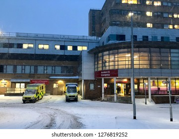 National Health Service, UK - 1st March 2018: Ambulances parked in snow with snowfall, in front of Emergency department of an NHS hospital. Conceptual image for winter