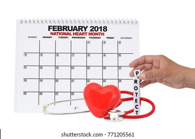 National Heart Month February 2018 Calendar Hand stacking Protect dice letters red heart and stethoscope on white background