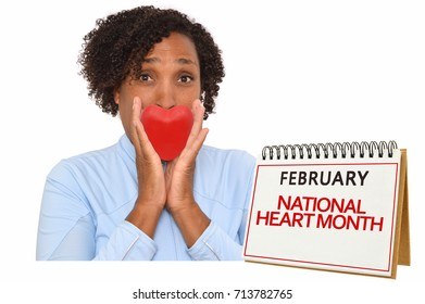 National Heart Month woman holding red heart looking at camera