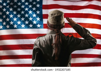 National holidays in the United States. A female soldier saluting, against the background of the American flag. Rear view. Copy space.