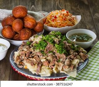 National Kazakh dishes - Beshbarmak, salad of radish Shalgam, and for dessert Baursak.